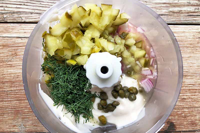 Horizontal image of prepped ingredients added to a food processor.
