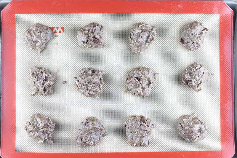 Horizontal image of 12 mounds of dough on a baking sheet lined with a silicone mat.