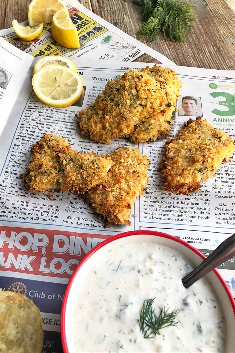 Vertical image of three pieces of breaded cooked meat on newspaper next to a bowl of a creamy dressing and lemon slices.