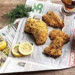 Horizontal image of three pieces of breaded and baked fillets on a newspaper next to lemons, herbs, and a bowl of a creamy white dressing.