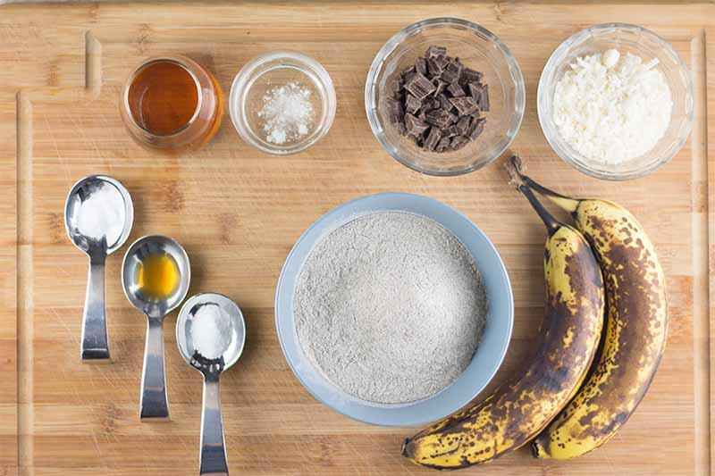 Horizontal image of two ripe bananas, wet ingredients, and dry ingredients on a wooden cutting board.