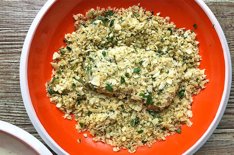 Horizontal image of coating a fillet in a seasoned breadcrumb mixture in a red plate.