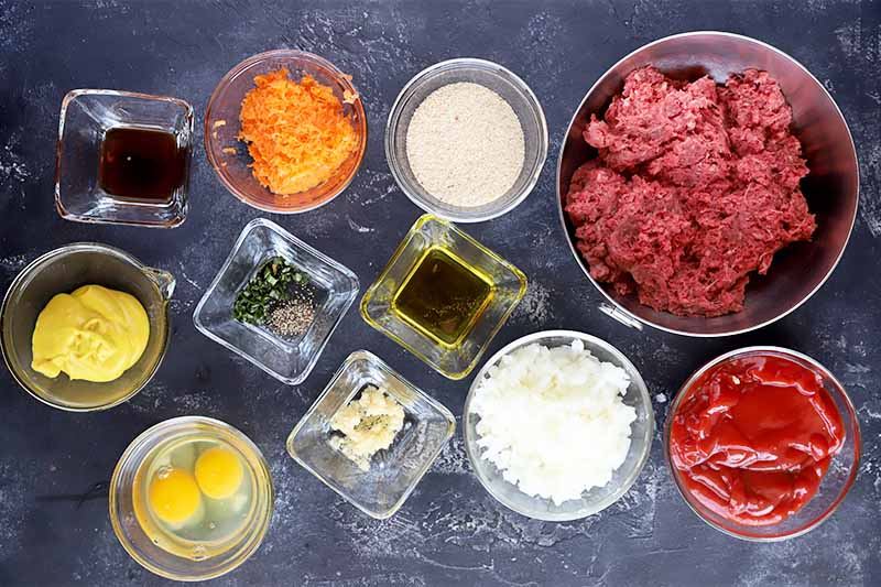 Horizontal image of assorted vegetables, seasonings, eggs and ground beef in various glass bowls on a gray surface.
