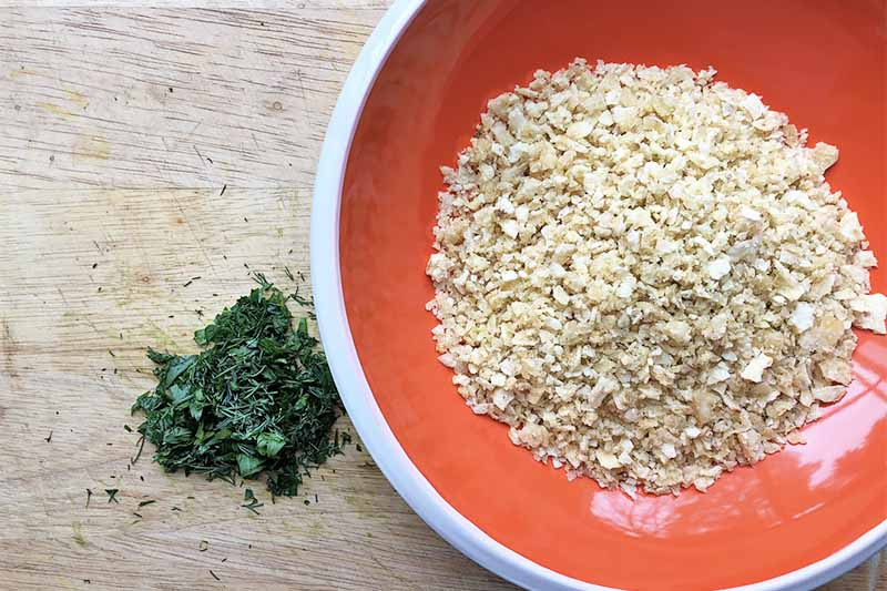Horizontal image of a red bowl with breadcrumbs next to chopped herbs on a wooden table.
