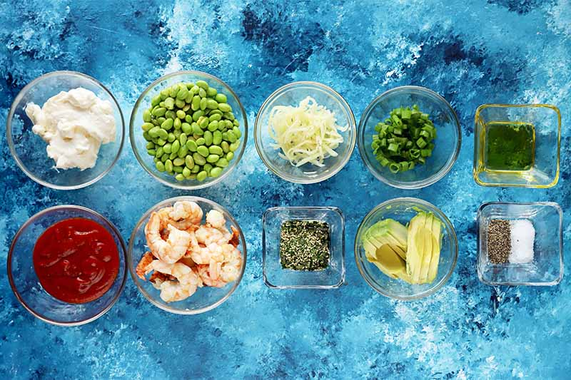 Horizontal image of assorted prepped fresh ingredients, seasonings, and shrimp in small glass dishes on a bright blue surface.