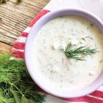 Horizontal image of a bowl full of a creamy white liquid toped with fresh herbs on a wooden table with a red and white towel and more fresh herbs.