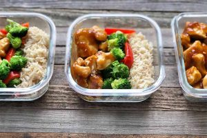 Horizontal image of three glass containers filled with portioned amounts of rice, vegetables, and chicken.