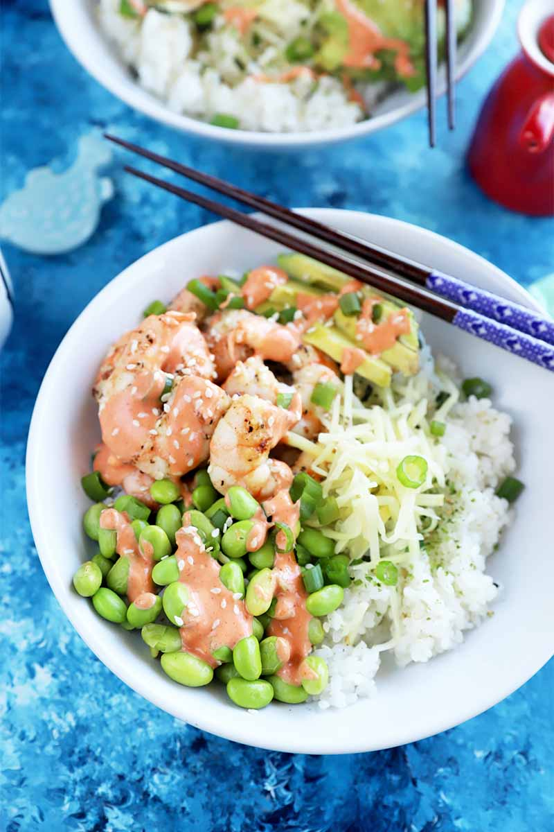 Vertical image of white dishes filled with rice, edamame, and shrimp drizzled with a light red sauce next to chopsticks on a blue surface.
