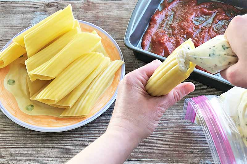 Horizontal image of hands filling hollow pasta shells with a ricotta mixture next to a pan spread with tomato sauce on the bottom.