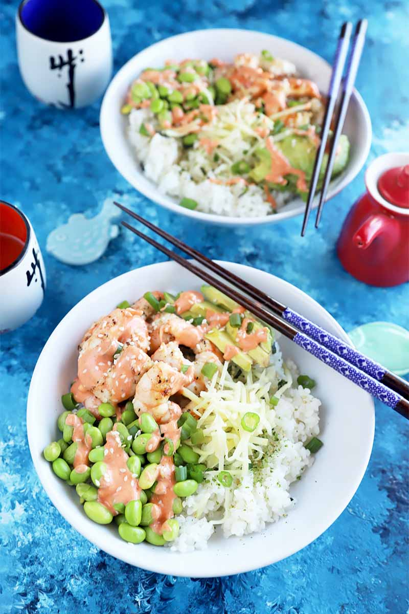 Vertical image of two white dishes filled with rice, edamame, seafood, and a drizzle of a red creamy sauce next to two pairs of chopsticks on a blue table.