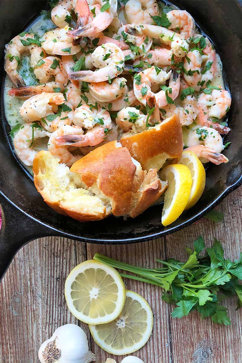Vertical image of a cast iron skilled filled with cooked seafood, chunks of bread, and lemon slices with a chopped parsley garnish on a wooden table next to more slices of lemons, whole parsley, and a whole head of garlic.