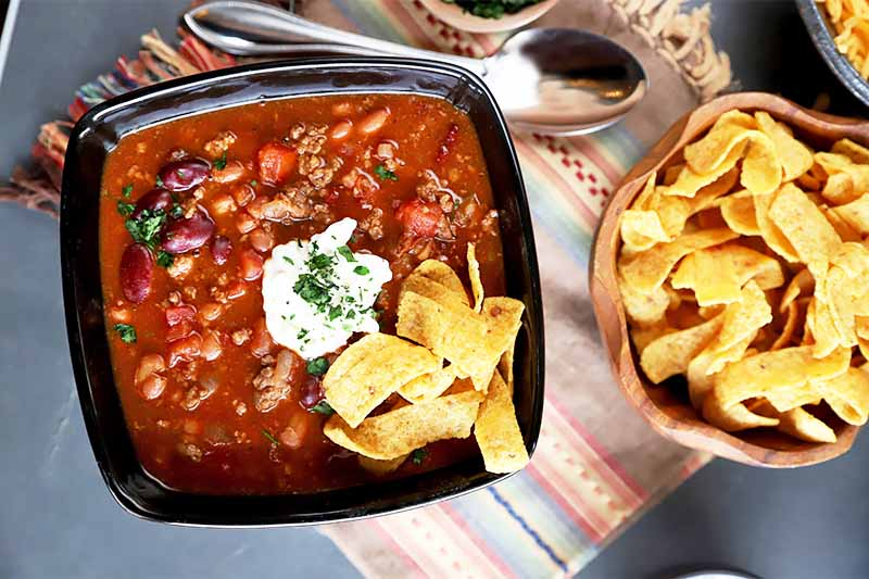 Horizontal top-down image of a black bowl filled with a deep red chunky stew garnished with nachos and sour cream next to a bowl of nachos on a brown striped napkin.