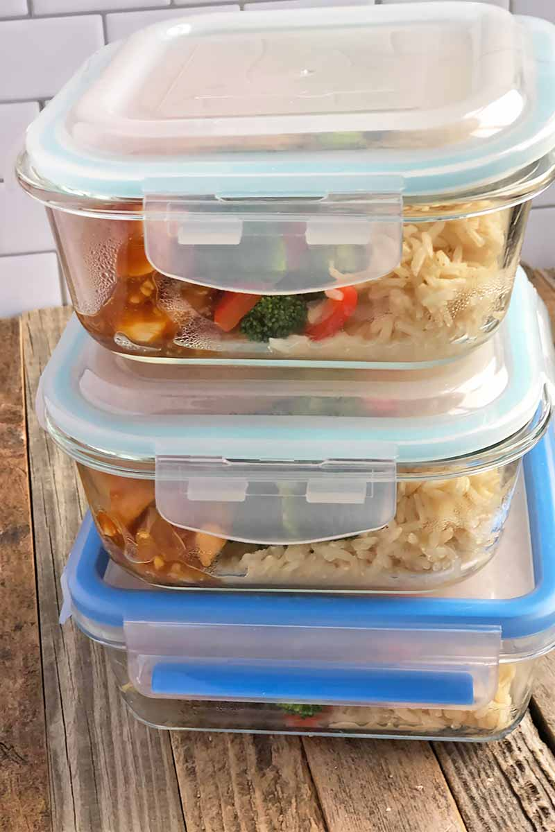 Vertical image of a stack of portioned dinners in containers with lids.