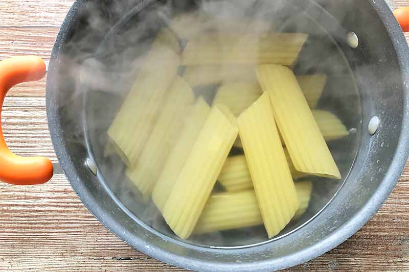 Horizontal image of cooked pasta tubes in a pot of hot water.