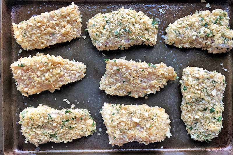 Horizontal image of breaded raw fillets on a baking sheet pan in rows.