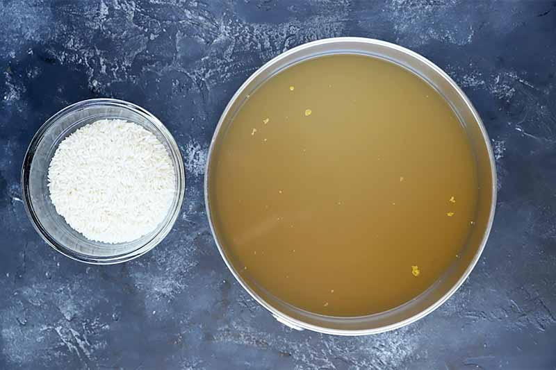 Horizontal image of a bowl of stock and a bowl of rice.