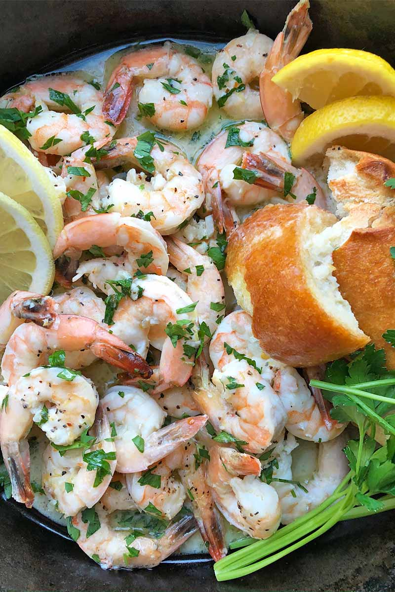 Vertical close-up image of a pan filled with cooked seafood next to lemon slices and bread chunks, garnished with chopped fresh green herbs.