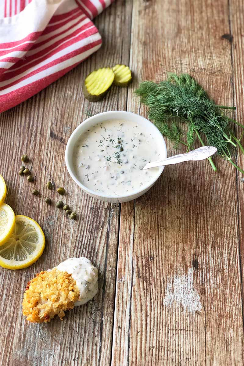 Vertical image of a bowl filled with a white, creamy condiment with a spoon next to capers, a breaded cooked meat, fresh herbs, and pickles on a wooden table.