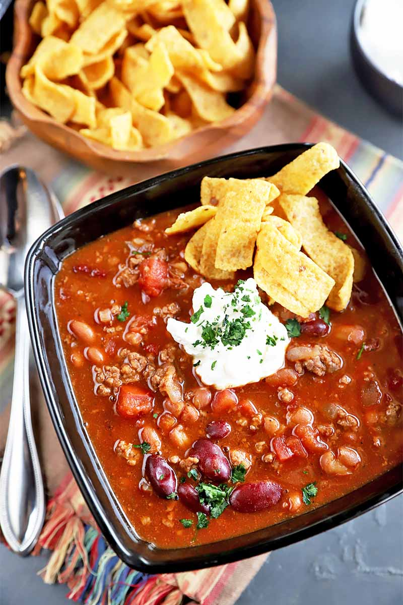 Vertical close-up image of a black bowl full of a chunky red stew garnished with sour cream, chips, and fresh herbs on a brown napkin next to a metal spoon and a bowl of chips.