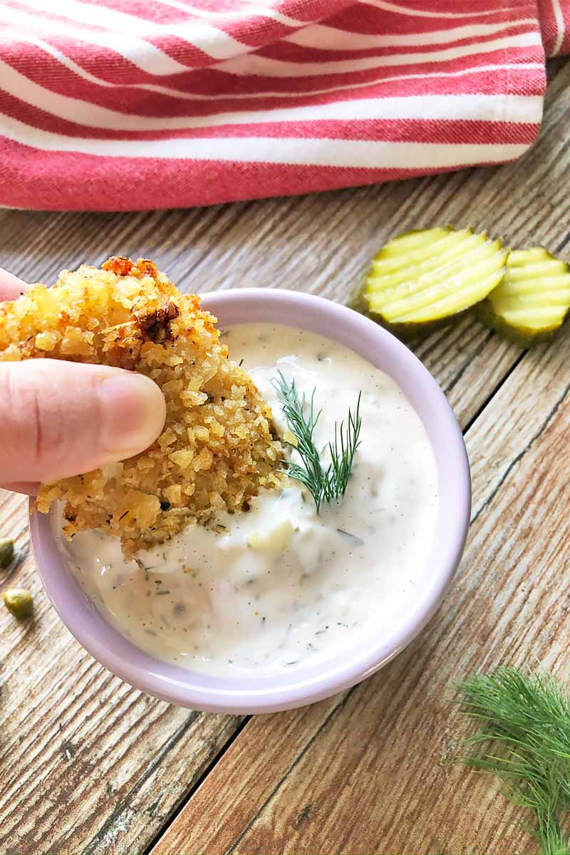 Vertical image of a hand dipping a piece of breaded cooked meat in a white condiment garnished with deal on a wooden table with pickles, capers, and a red and white towel.