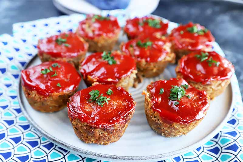 Horizontal image of small ground beef rounds baked and topped with ketchup on a blue plate.