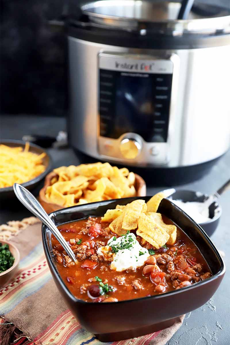 Vertical image of a black bowl full of a red chunky stew with a metal spoon and garnished with sour cream and chips, with an appliance in the background.