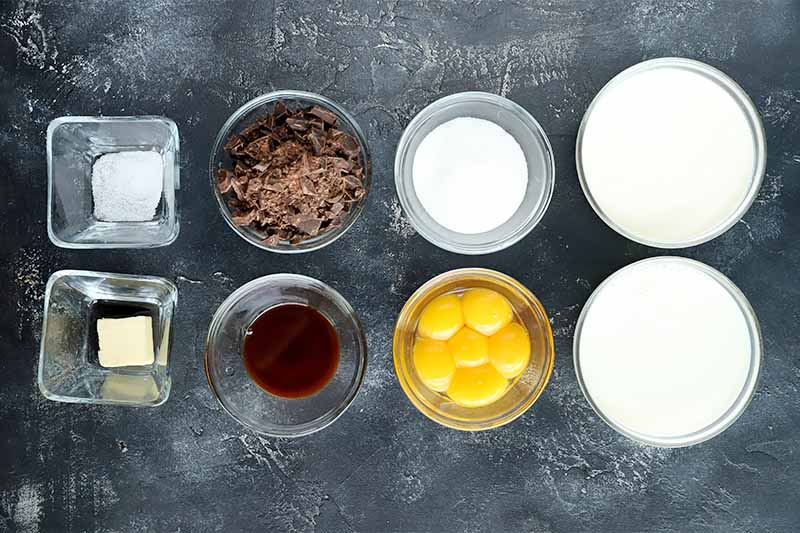 Horizontal image of prepped and measured ingredients in bowls on a gray surface.