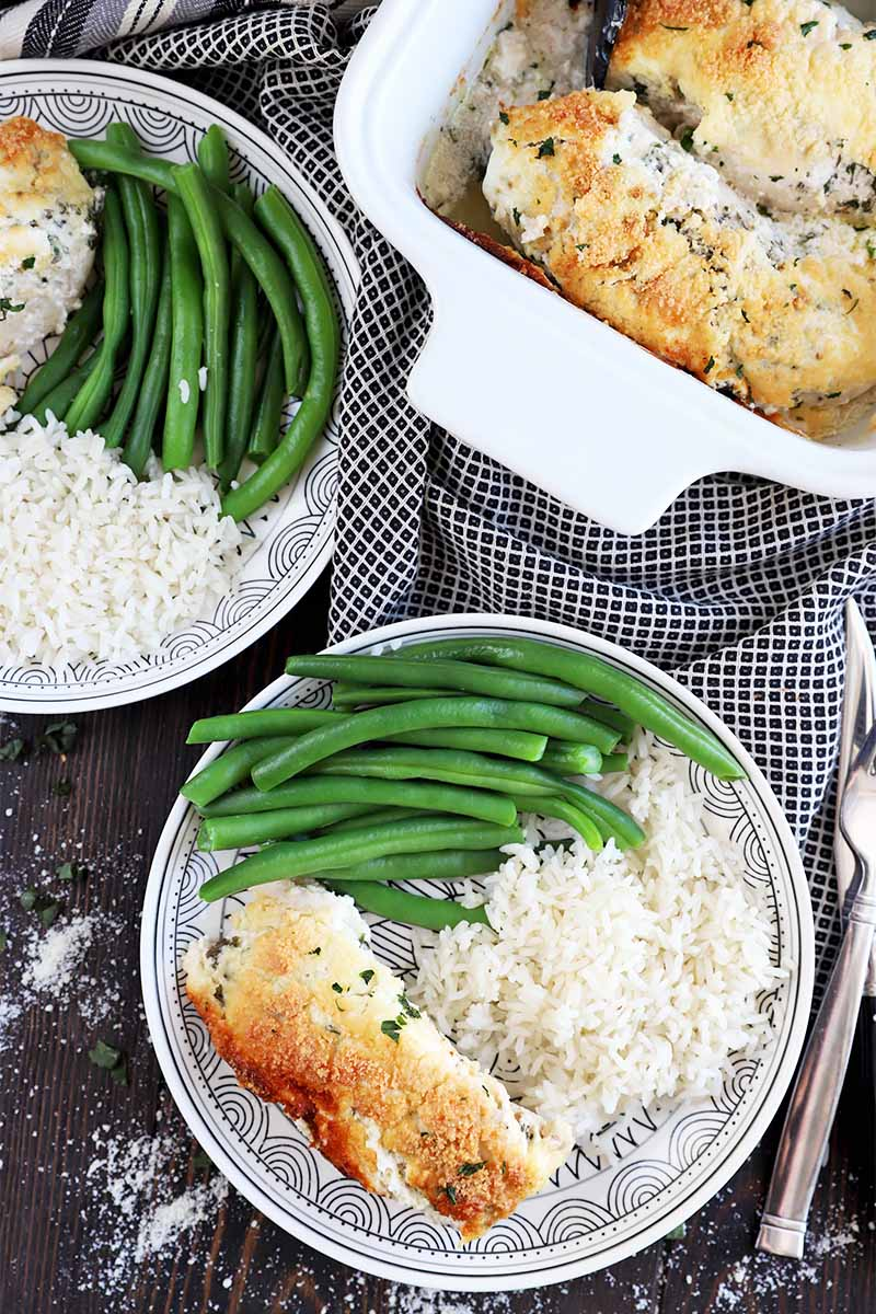 Vertical top down image of two plates with green beans, white rice, and a breaded meat fillet next to a casserole dish and silverware.
