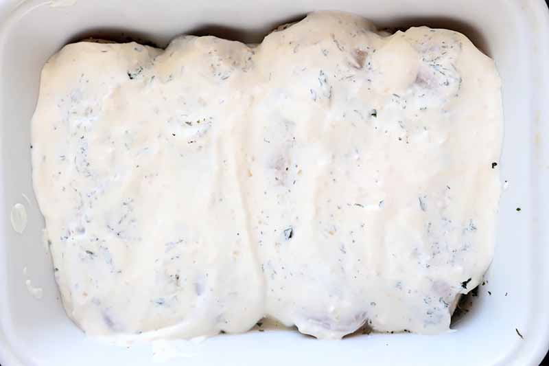 Horizontal image of raw poultry breasts covered in a yogurt sauce in a white dish.
