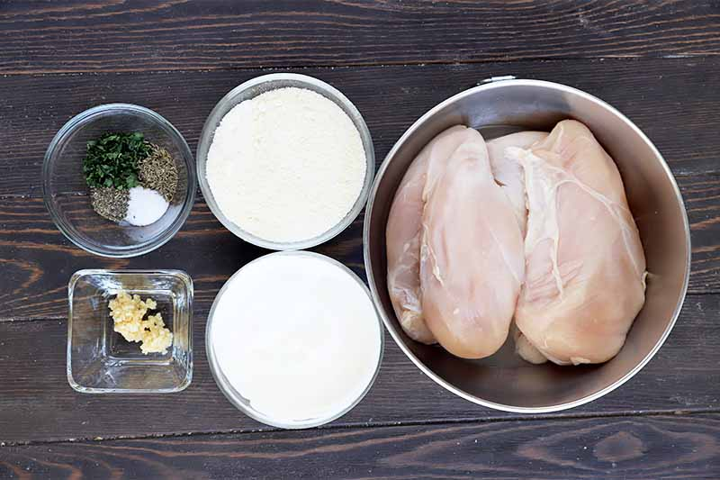 Horizontal image of a bowl of raw poultry breasts, grated cheese, yogurt, and seasonings in bowls.