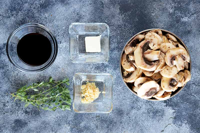 Horizontal image of bowls of garlic, butter, soy sauce, and sliced tan vegetables next to a small mound of fresh thyme.