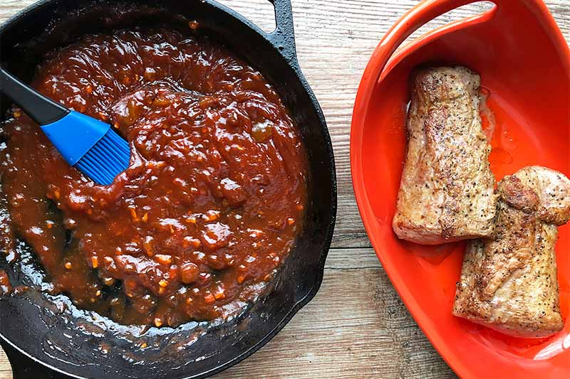 Horizontal image of a thick red liquid in a cast iron skillet next to two pieces of cooked meat in a red dish.