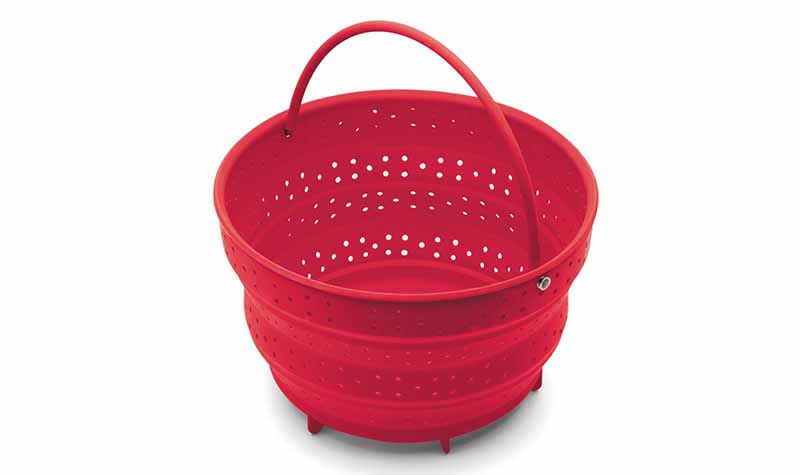 Horizontal image of a red steamer basket.