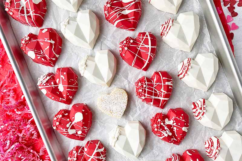 Horizontal top-down image of neat rows of decorated red and white candies on a sheet pan lined with parchment paper.