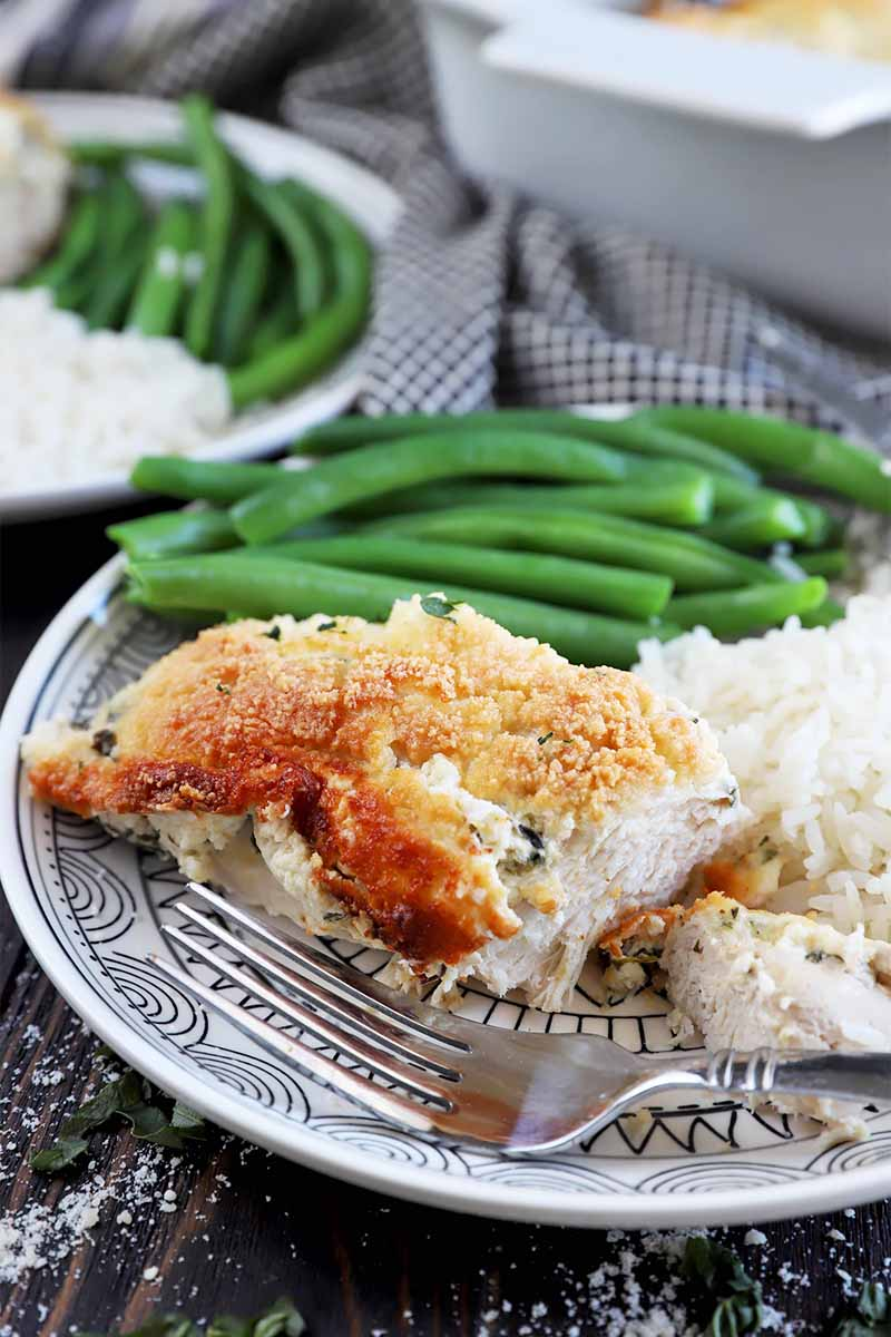 Vertical image of a metal fork, half-eaten piece of breaded cooked meat, green beans, and rice on a patterned plate.