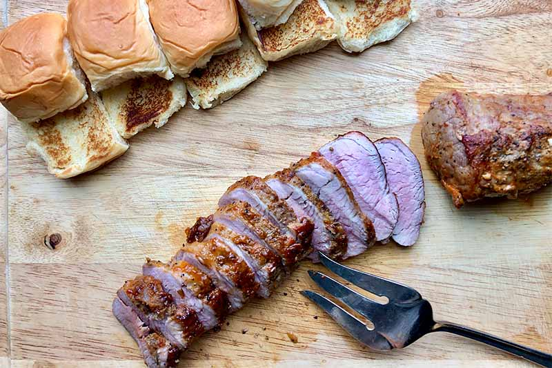 Horizontal image of toasted mini buns, sliced meat, and a metal fork on a wooden board.
