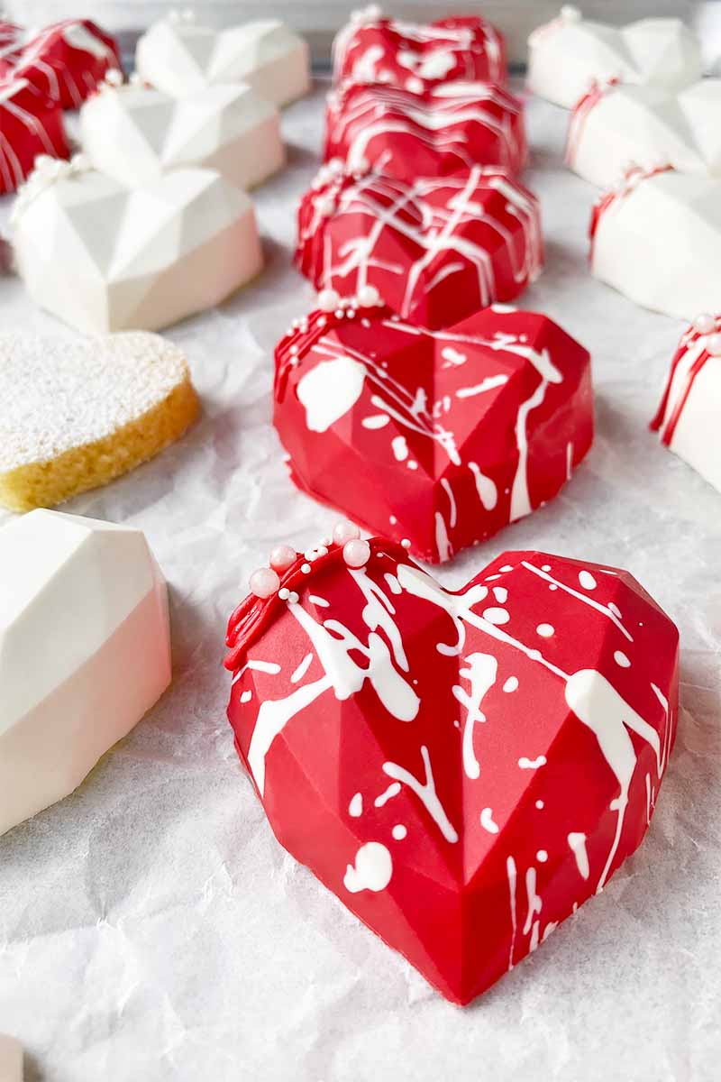 Vertical image of rows of red and white heart-shaped candy molds, with some decorated in a paint splatter.