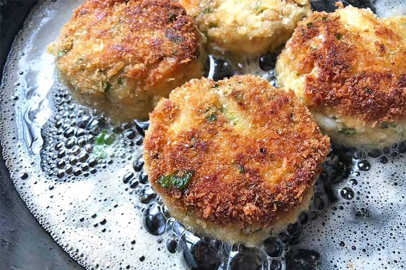 Horizontal image of searing small patties in a skillet with oil.