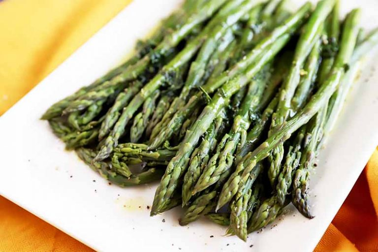 Horizontal image of a white plate with a mound of cooked long green vegetable spears seasoned with oil, salt, and pepper on a yellow towel.
