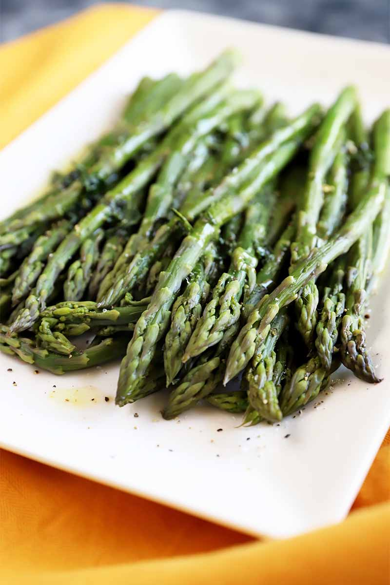 Vertical image of a white plate full of cooked, lightly seasoned, long green vegetable spears on top of a yellow towel.