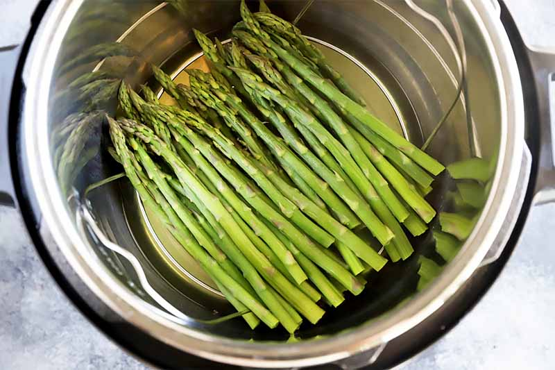 Horizontal image of a bunch of long, green vegetable spears in a colander insert in a metal appliance.
