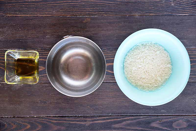 Horizontal image of a bowl of oil, a bowl of water, and a bowl of uncooked white grains.