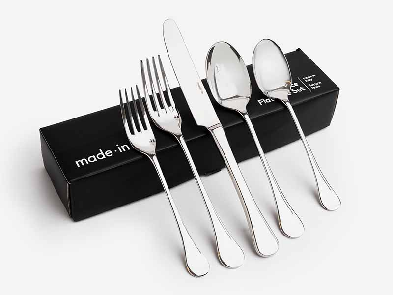 Horizontal image of metal utensils leaning up against a black box.