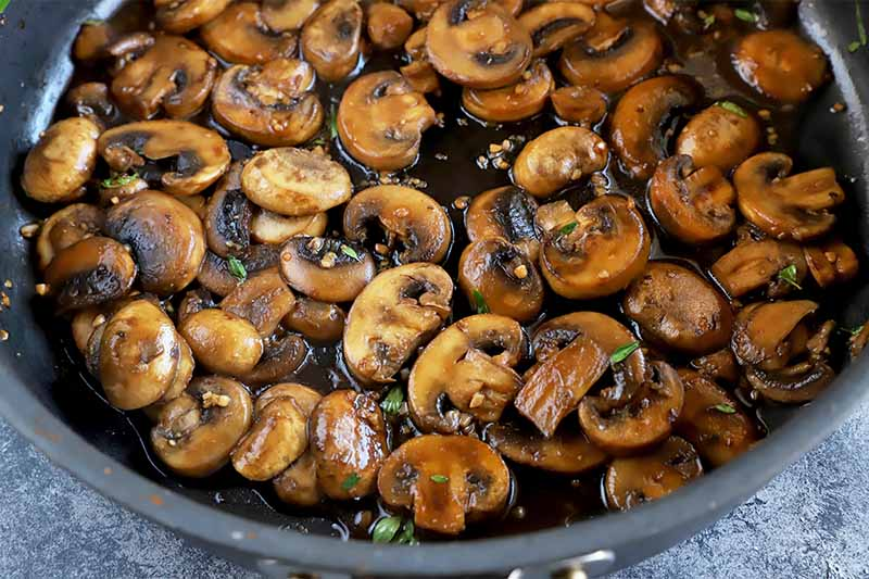 Horizontal image of cooked sliced tan edible fungi in a pan covered in a dark sauce and fresh herbs.