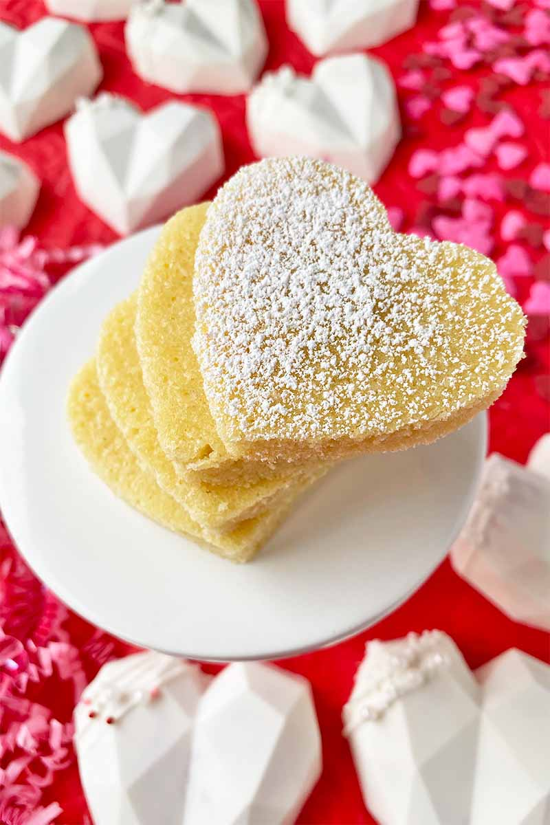 Vertical image of a stack of heart-shaped desserts dusted with powdered sugar on a white stand surrounded by white candies.