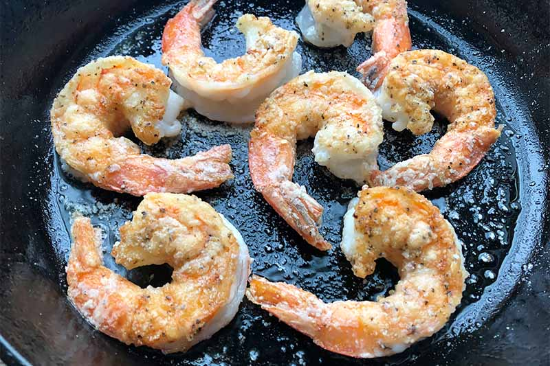 Horizontal image of cooking shrimp in a cast iron skillet.