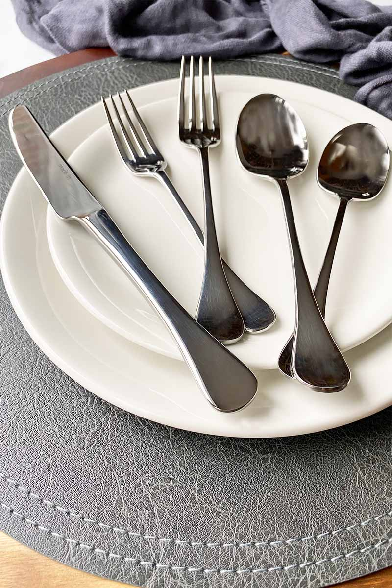 Vertical image of metal utensils on two sets of white plates on a gray placemat.