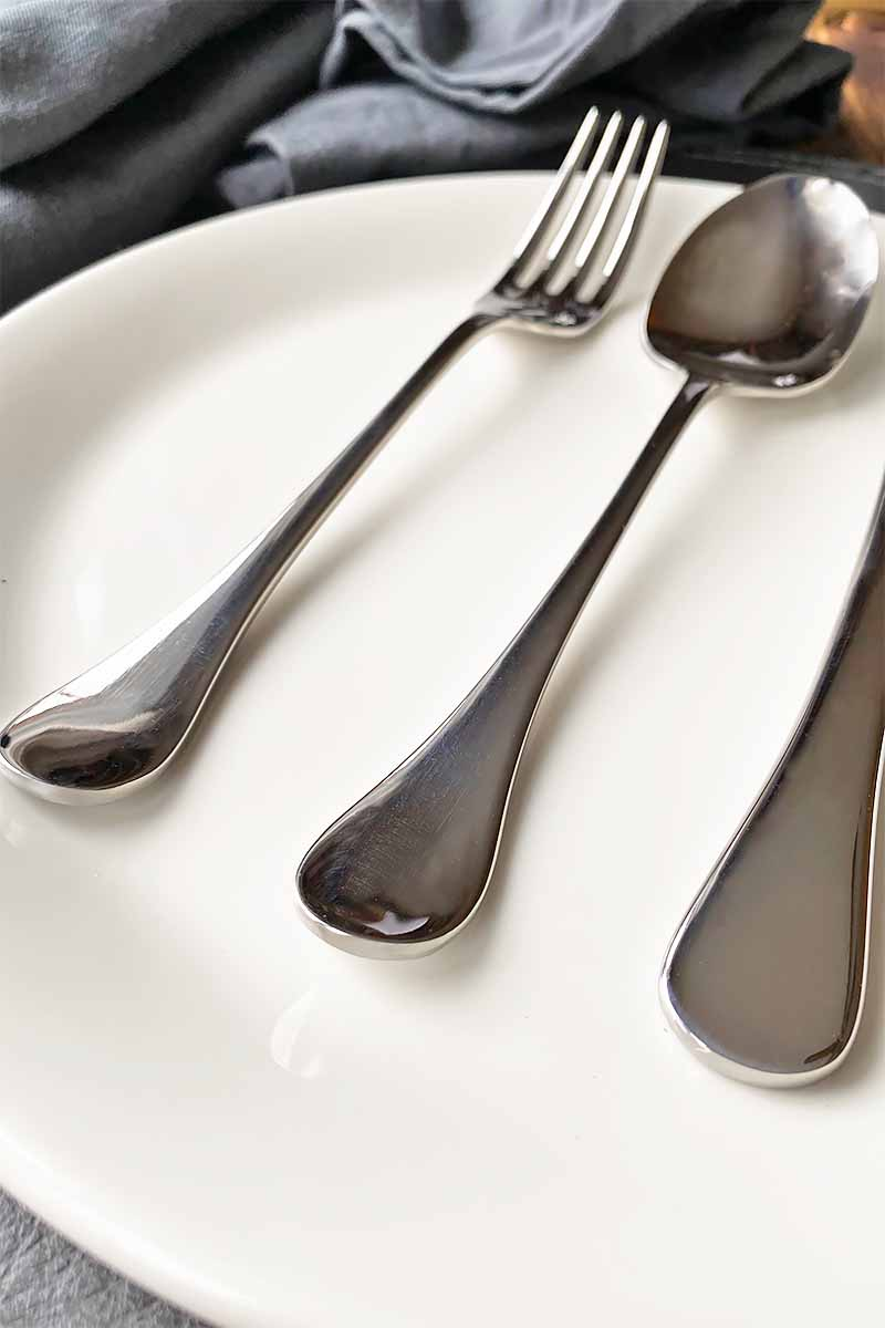 Vertical close-up image of the handles of a metal fork and spoon on a white plate.
