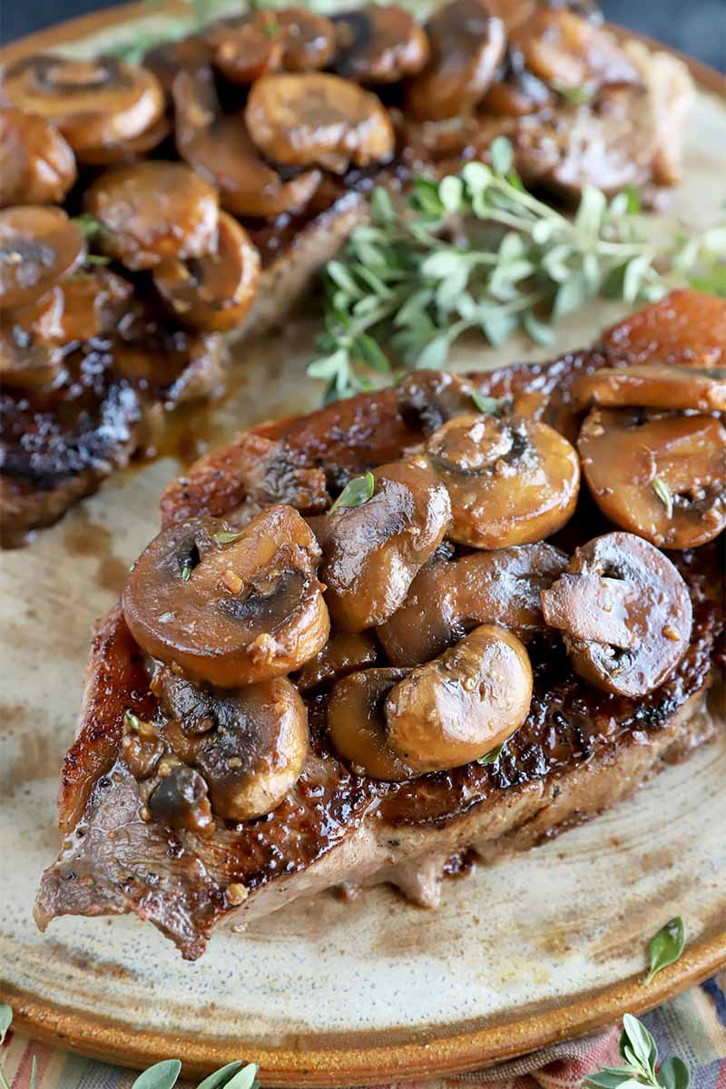 Vertical close-up image of steaks topped with browned slices of vegetables on a tan plate next to fresh herbs.