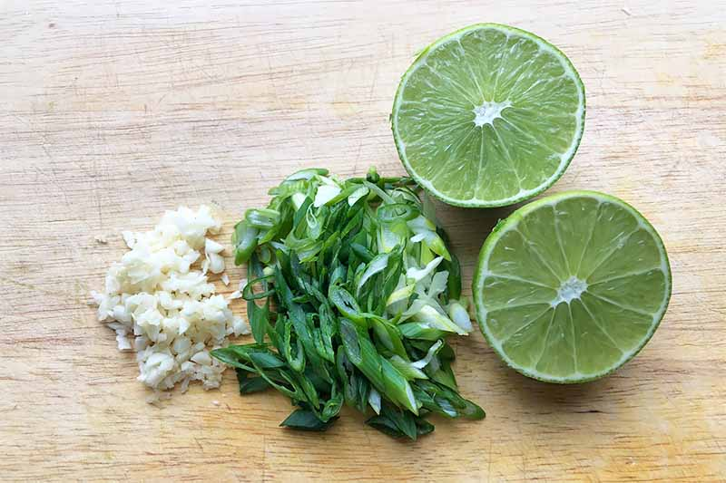 Horizontal image of a halved lime, sliced scallions, and minced garlic on a wooden cutting board.